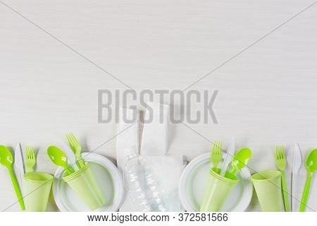 Plastic Disposable Dishes. Food Plastic On Wooden Background Top View. Recycling Plastic And Ecology