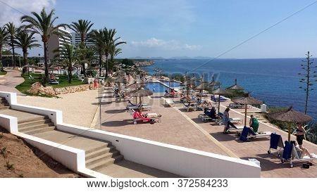 Majorca, Spain - June 18, 2018: Rest In A Resort On The Coast Of Majorca, Spain. People On Sunbeds U