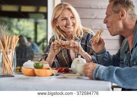 Happy Elderly Spouses Enjoying Meals In Veranda