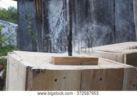Drilling A Hole In A Wooden Board At High Speed There Is Smoke