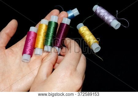 Female Hands Hold Skeins Of Thread. Silk Threads For Embroidery. Skeins Of Yellow, Blue, Green Pink,