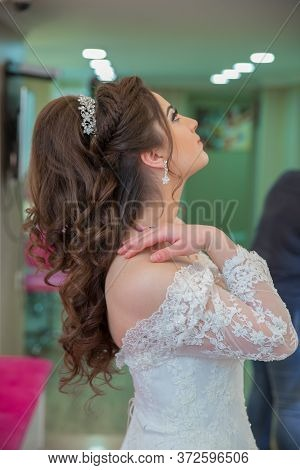The Bride Puts Her Hand On Her Shoulder And Takes A Picture At The Wedding. Wedding Photo Session In