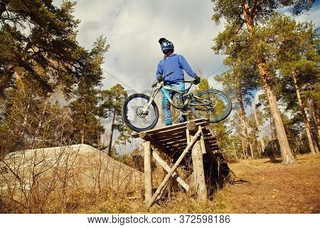 Man In Helmet With A Mountain Downhill Bike.
