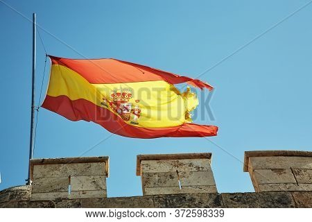 Tattered Half-mast Mourning Spanish Flag At The Top Of A Fortress On A Sky Background.