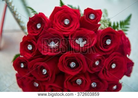 Set Of Wedding Rings In Red Rose Taken Closeup . Bride And Groom Rings On A Red Wedding Bouquet. A B