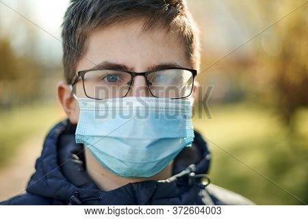 Difficulty Of Entering The Mask Fog Up The Glasses. Guy In A Medical Mask And Glasses Outdoors.
