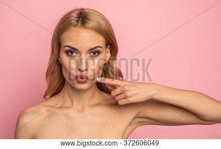 Funny Attractive Big-eyed Girl Pointing On Pout Lips With Forefinger, Showing Effect After Lifting P