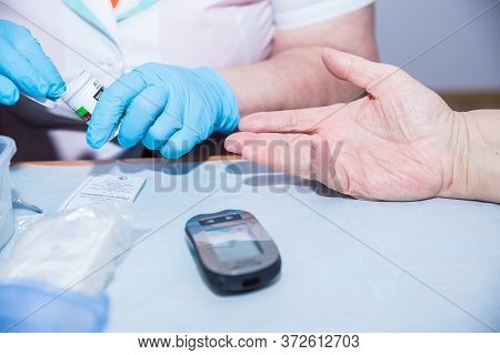 Moscow, Russia, May 4, 2020.female Doctor Measures Mans Blood Sugar Level Using Glucose Meter. Expre