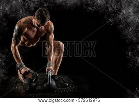 Sporty man workout with kettlebell. Sports banner. Horizontal copy space background