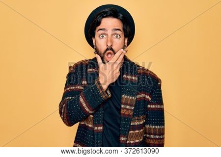 Young handsome hispanic bohemian man wearing hippie style and boho hat Looking fascinated with disbelief, surprise and amazed expression with hands on chin