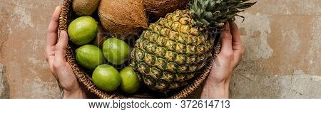 Cropped View Of Woman Holding Ripe Exotic Fruits In Wicker Basket On Weathered Surface, Panoramic Cr