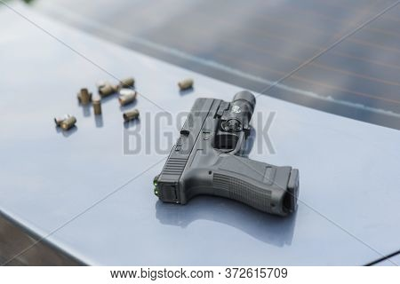 Hand Gun With Bullets And Sleeves On The Trunk Of The Car. Stop Terrorism And Crime.