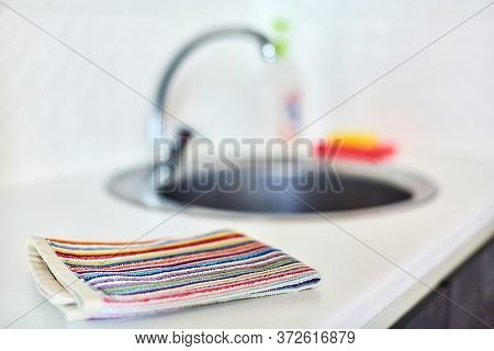 Kitchen Towel And Sink Without Dirty Dishes Background. Dishcloth On Kitchen Countertop. Cleaning An