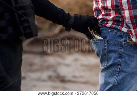 The Thief In Black Clothes And Gloves Stealing A Wallet With Money From Pocket. Pickpocketing On The