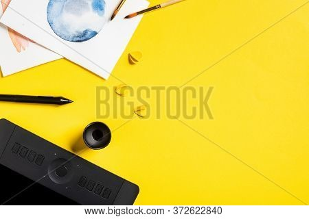 Top View Of Paintbrushes Near Paintings, Paper Cut Elements, Drawing Tablet And Stylus On Yellow