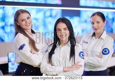 group portrait of female security operator while working in a data system control room offices Technical Operator Working at  workstation with multiple displays, security guard working on multiple