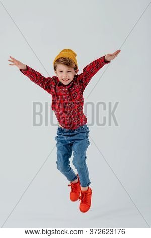 Cheerful Kid In Checkered Shirt And Jeans Jumping With Outstretched Arms On White Background In Stud