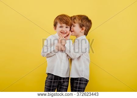 Content Twin Brothers Wearing Classy Clothes Standing In Studio On Yellow Background And Whispering