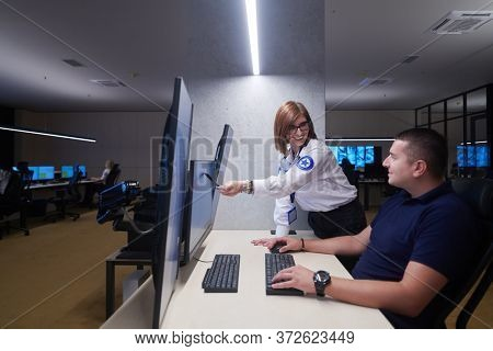 Group of Security data center operators working in a CCTV monitoring room looking on multiple monitors  Officers Monitoring Multiple Screens for Suspicious Activities  Team working on the System Contr