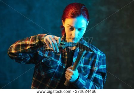 Girl Builder Holds Hammer And Pliers In His Hand. Young Woman In Plaid Shirt. Incompetent Worker Con