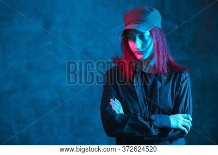 Red Haired Girl In Cap And Black Shirt On Dark Background With Colored Neon Lighting. Solitude And L