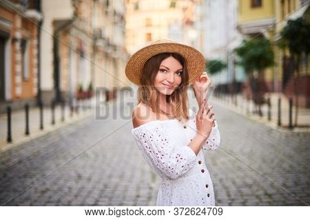 Portrait Cheerful Tourist Woman Standing On Ancient Street In Old Town. Attractive Woman In Straw Ha