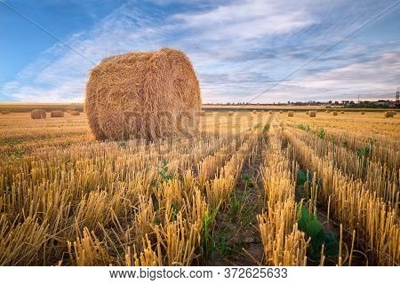 Beautiful Countryside Landscape. Round Straw Bales In Harvested Fields And Blue Sky With Clouds.