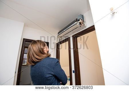 Side View Of Young Woman Admiring The Newly Installed Unfinished Ac Air Conditioning Unit Inside Her