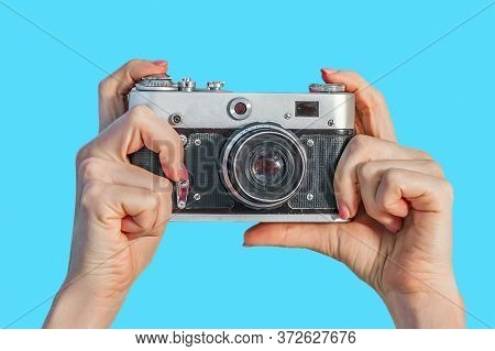 Retro Camera In Female Hands Close-up On A Blue Background. Woman Hands Holding Retro Camera Isolate