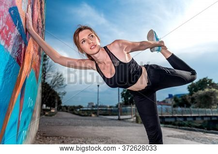 Young Woman Doing Gymnastics On The Street. Young Woman Doing Sport Exercise Against Colorful Wall O