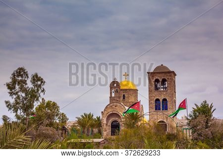 Qasr el-Yahud is the site of the baptism of Jesus Christ by John the Baptist. Church of John the Baptist. Jordanian national flags fluttering on Jordanian side. The concept of religious tourism