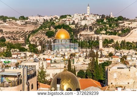 Bird's eye view. The golden dome of the mosque of Omar.The walls of the mosque are blue mosaic. The roofs of Jerusalem. Sunset. The concept of historical, religious, pilgrim and photo tourism