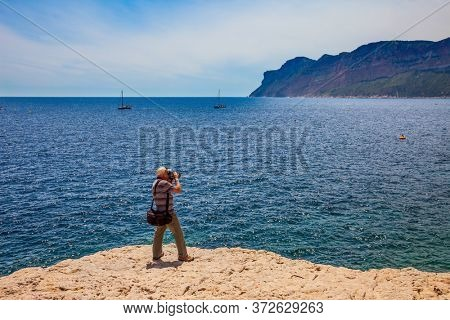 Tourist with a photo bag photographed landscape. Bays of the Mediterranean Sea and the Cote d'Azur. Calanques are the attractions of Provence. French. The concept of photo tourism