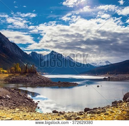 Canada, Alberta, Jasper Park. Lake Medicine. Great autumn day. The sun illuminates the snow-capped mountains. The concept of active, ecological and photo tourism