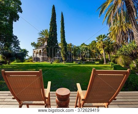 Two comfortable wooden chairs - deck chairs for relaxing. Catholic Church of the Beatitudes and park around the monastery. The concept of religious pilgrimage and photo tourism