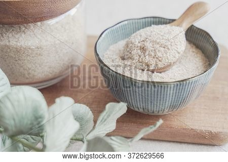 Psyllium Husk In Wooden Spoon And Bowl On Wooden Plate, Superfood Fiber Prebiotic Food For Gut Healt
