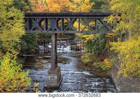 Autumn Background. Railroad Bridge Over A River With A Waterfall In The Background Surrounded By Vib