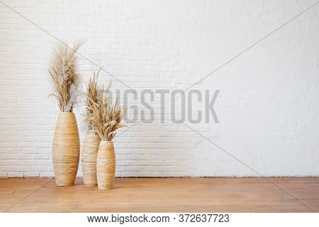 Three Wicker Vases With Dry Pampas Grass Against A White Textured Brick Wall. Blank For Interior Des