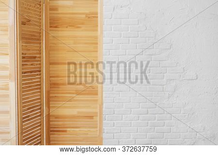 Louvered Wooden Screen On A White Brick Wall Background With Copy Space.