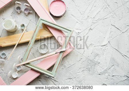 Several Wooden Frames, Paint Brushes And Paint Cans On Gray Gray Background With Copy Space. Worksho
