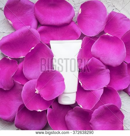 White Mock-up Tube Of Cream On A Background Of Pink Rose Petals.
