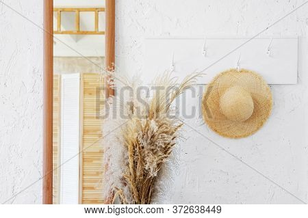 Wicker Hat On A White Wooden Hanger In A Minimalistic Interior. A Mirror And A Bouquet Of Dry Spikel