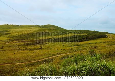 A Pacifying Landscape - A Road Stretching Into The Distance Against The Backdrop Of Green Hills.