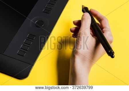 Cropped View Of Man Holding Stylus Near Graphics Tablet On Yellow Surface
