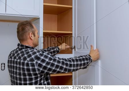 Master Adjusts Fixing In The Hinge Of The Kitchen Cabinet Door With Screwdriver.