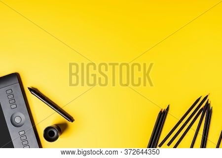 Top View Of Drawing Tablet And Pencils Near Stylus On Yellow