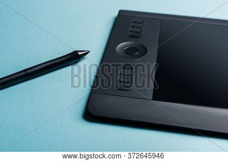 Close Up View Of Graphics Tablet And Stylus On Blue Surface