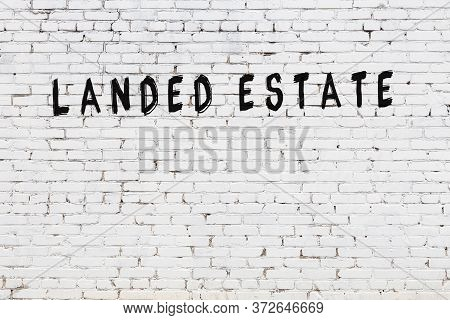 White Brick Wall With Inscription Landed Estate Handwritten With Black Paint