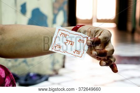 A Lady Holding A Piece Of Paper With Name Of Lord Ram Written On It On The Occasion Of Raksha Bandha