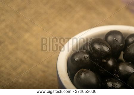Black Seedless Olives In A Ceramic Bowl On A Background Of Coarse-textured Fabric. Close Up.